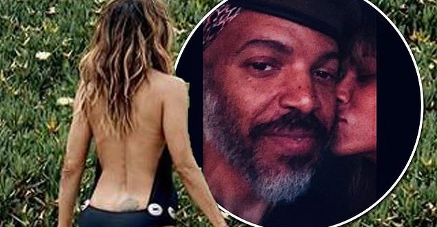 Halle Berry, 54, shows off her age-defying physique in a backless black swimsuit