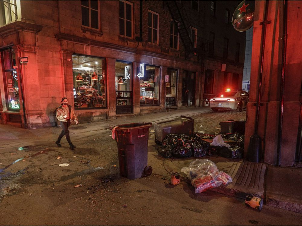 A woman walks by damage on St-Paul St. W. that was made when a crowd of at least several hundred people gathered in Old Montreal, chanting and shooting off fireworks to protest the return to an 8 p.m. curfew in Montreal.