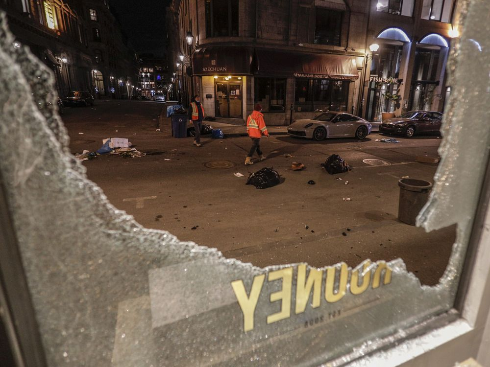 Workers look over damage on Notre-Dame St. W. outside of Rooney Shop in Old Montreal Sunday, April 11, 2021.