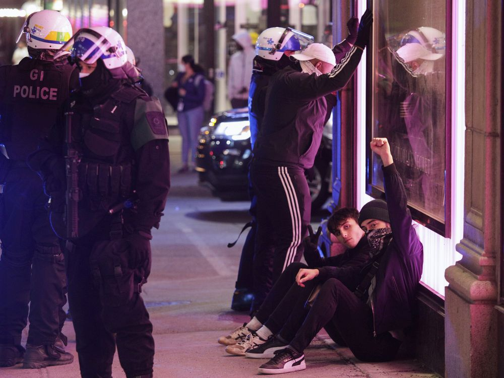 Young men are detained by Montreal police in downtown Montreal Monday, April 12, 2021. Protesters against COVID-19 restrictions set by the Quebec government were out after the 8 p.m. curfew.