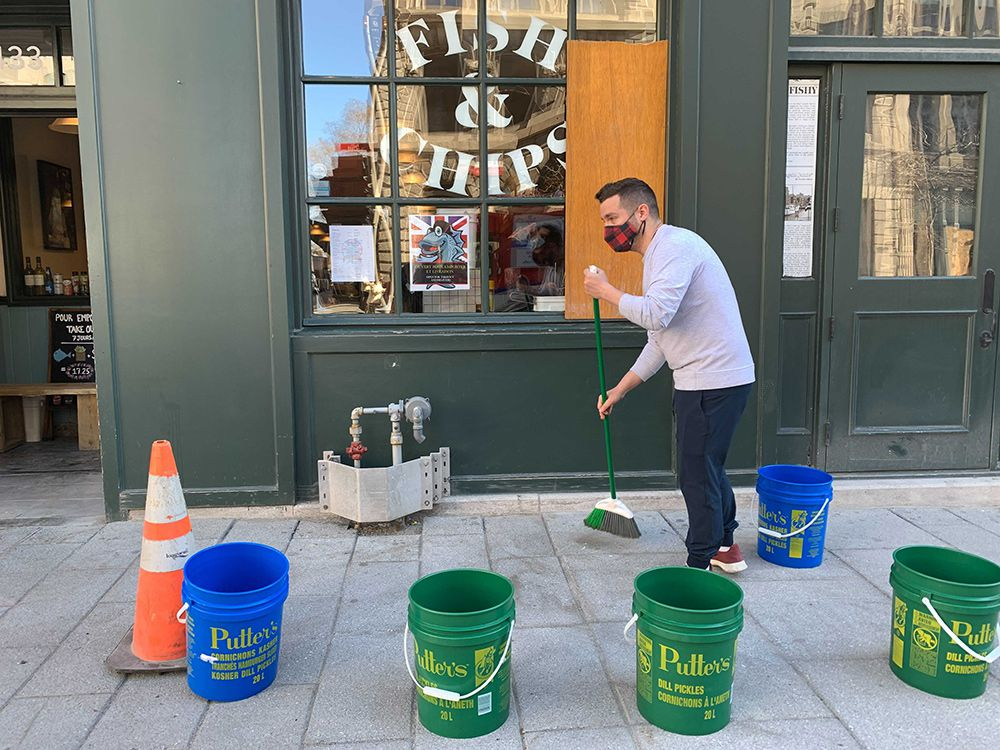 Restaurant co-owner Rob Stutman cleans up on April 12, 2021, following the previous night's anti-curfew riots in Old Montreal.