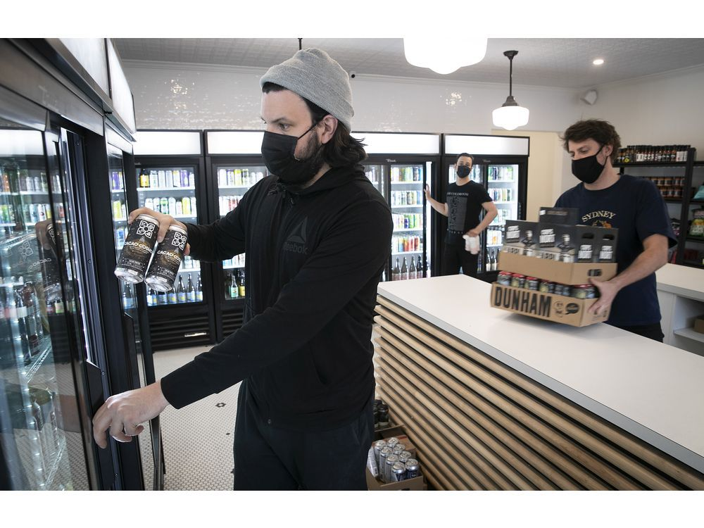 MONTREAL, QUE.: APRIL 23, 2021 — Kevin Demers stocks one of the beer fridges at Dépanneur Bière Froide Cold Beer during the COVID-19 pandemic. With Demers are co-owners Sam Kirk, far right, and Fred Masse, in background.