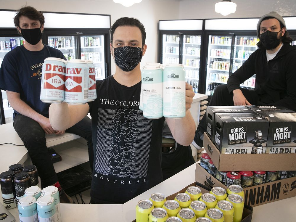 Fred Masse holds four packs of beer with co-owners Sam Kirk, left, and Kevin Demers, at the Dépanneur Bière Froide Cold Beer, on April 23, 2021, during the COVID-19 pandemic.