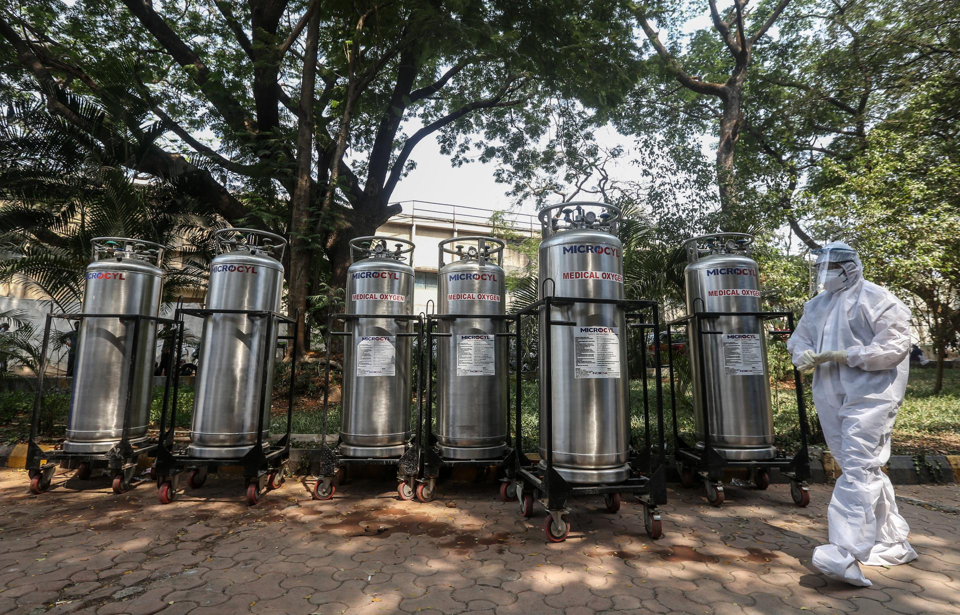 An Indian worker stands near oxygen cylinders at a jumbo Covid-19 centre in Mumbai. EPA