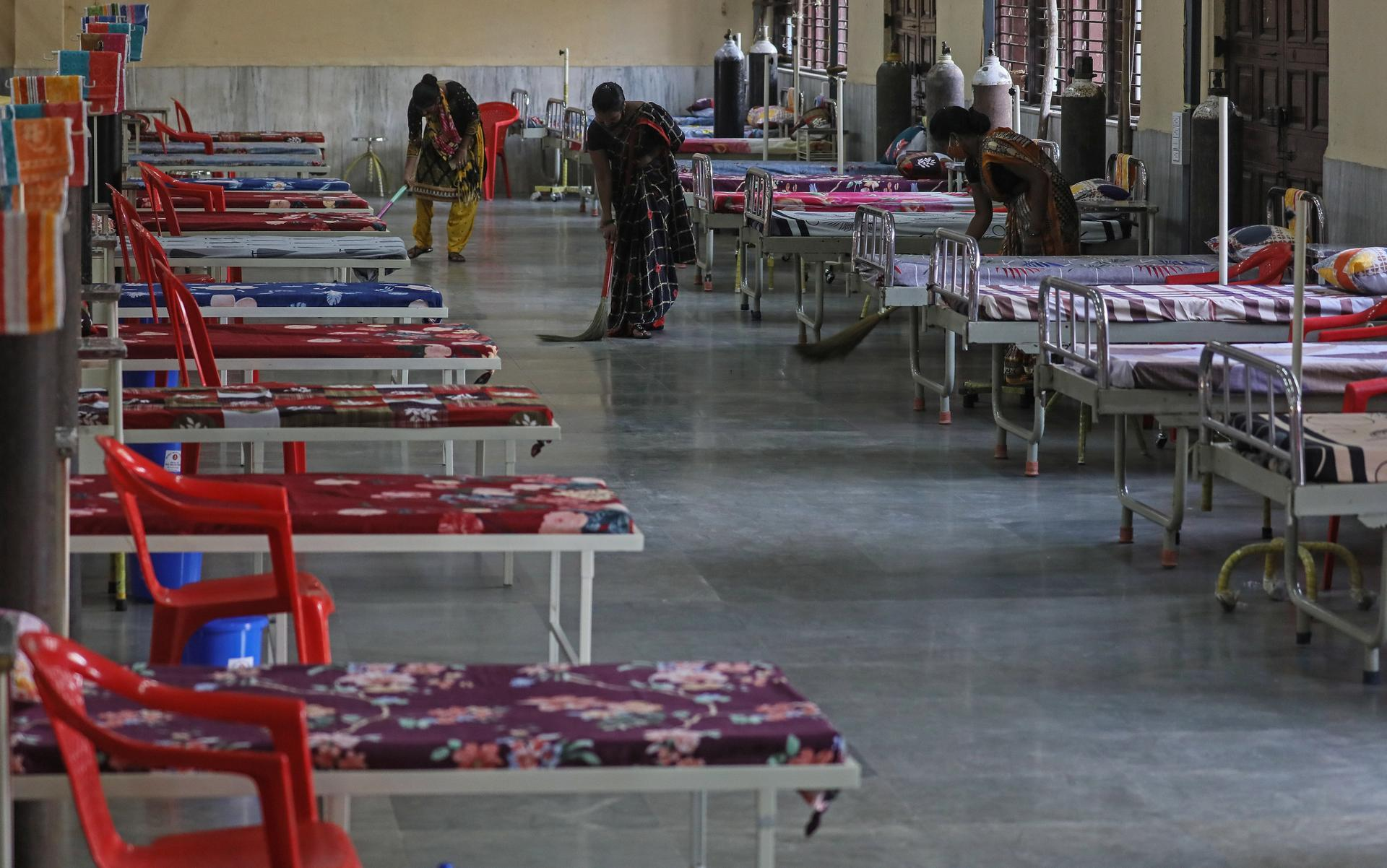 Workers clean the floor near the beds inside a newly opened Covid-19 centre in Mumbai. EPA