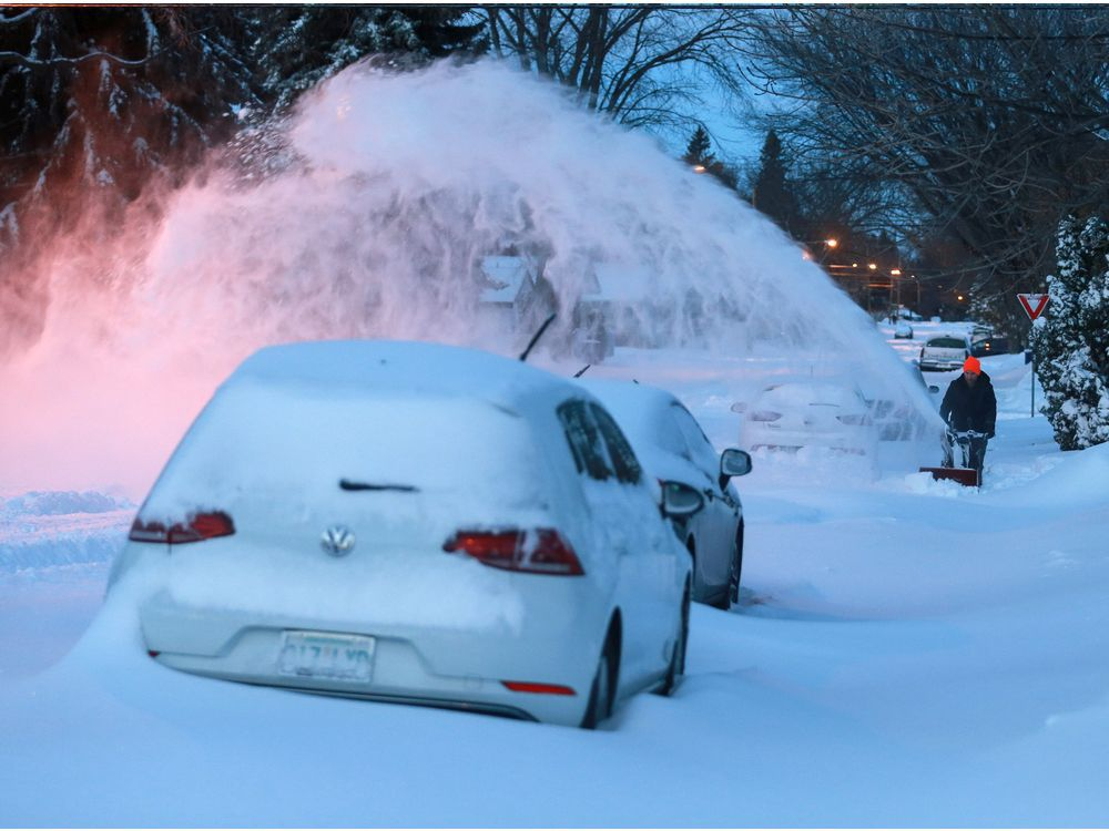 Saskatoon residents clear snow Monday morning after a record-breaking snow fall.