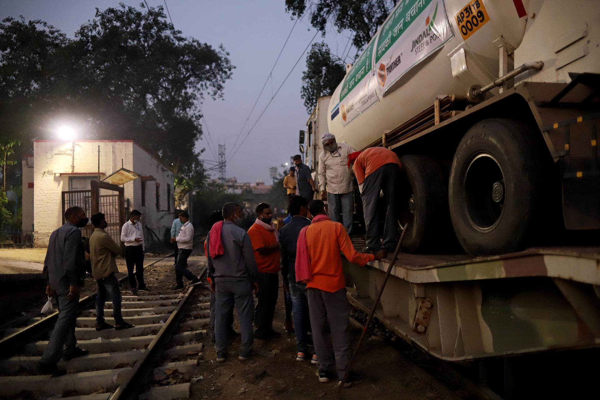 Workers unload a medical oxygen tanker from the 'Oxygen Express' train at Delhi Cantonment railway station. Bloomberg